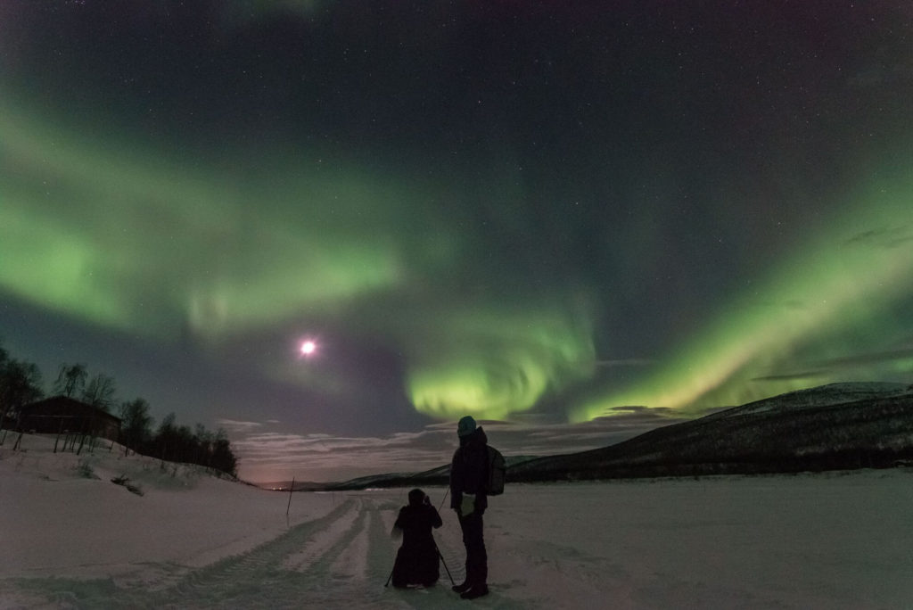 Tourists enjoying their northern lights holidays in Finlandunder the full moon on the ice of the Teno River in Utsjoki