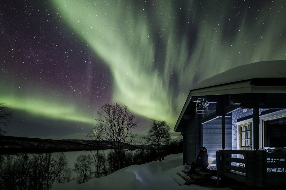 northern lights above a cottage of Aurora Holidays in Lapland